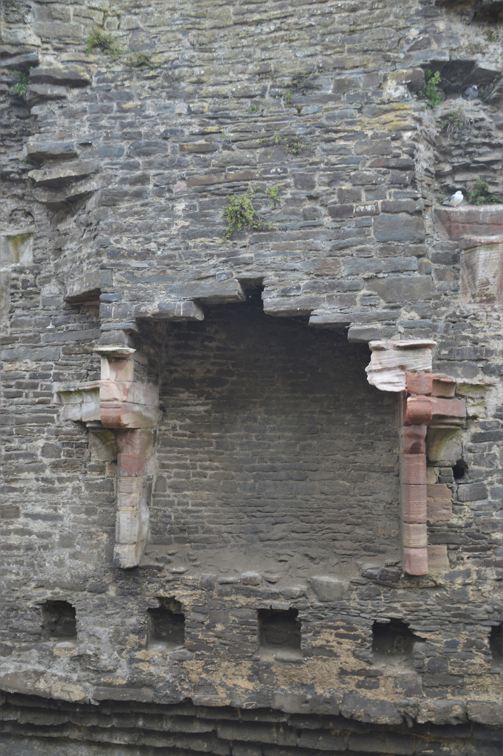 Decorative stonework of the fireplace in the Great Hall of Conwy Castle. Post posts in the stone work that supported the floor