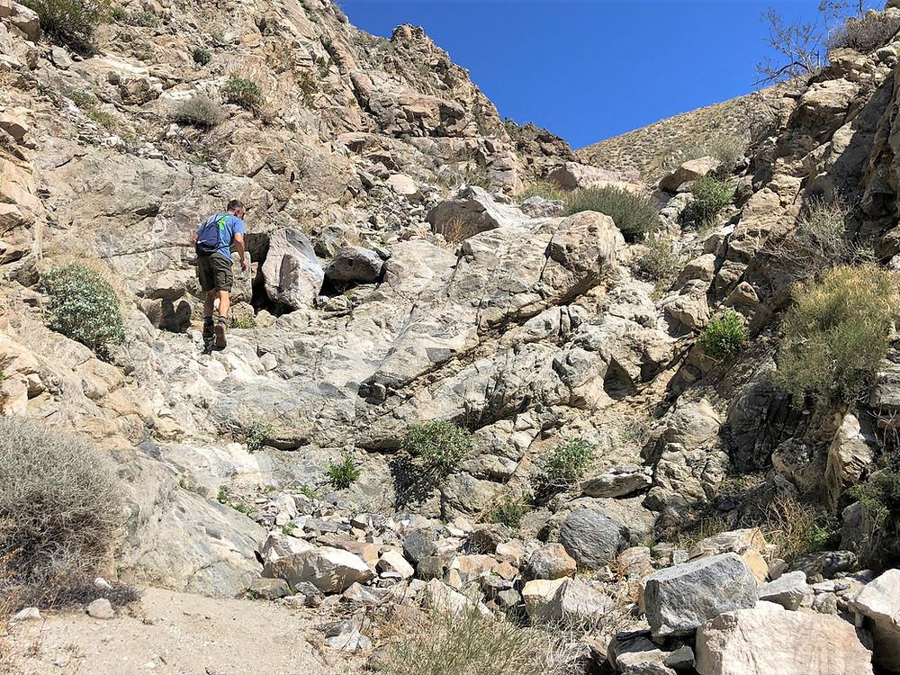Climbing rocky ledge in Swiss Canyon trail in Little San Bernardino mountains