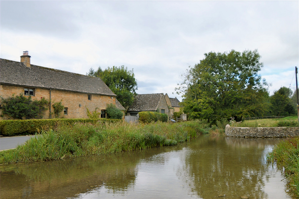Homes made of Cotswold yellow limestone along River Eye in Lower Slaughter. Cotswolds.