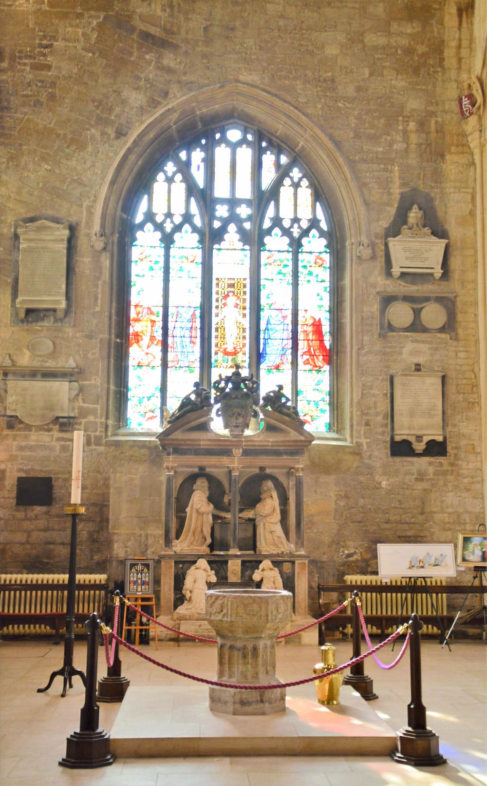 14th century baptismal font and tomb of George Monox in Cathedral of the Cotswolds, St. John the Baptist in Cirencester of the Cotswolds