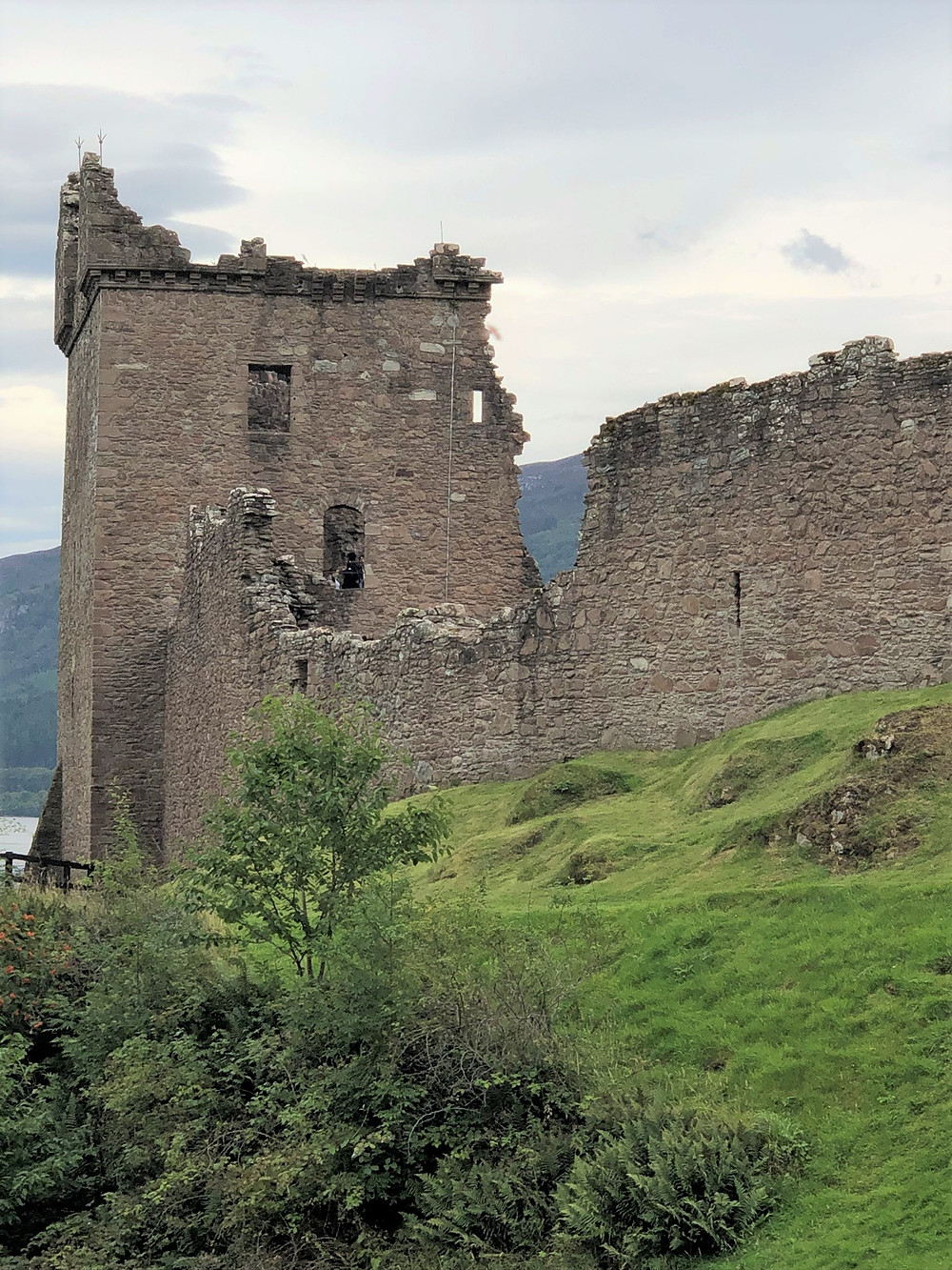 Ruins of Urquhart castle towers and walls sits on the banks of Loch Ness