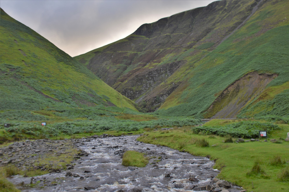 Hike through green valleys to Grey Mare's Tail waterfall in Southern Scotland
