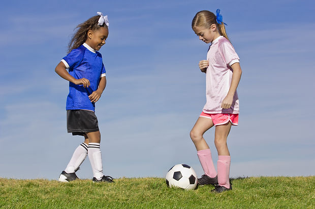 Two young girls playing soccer (simple background).jpg