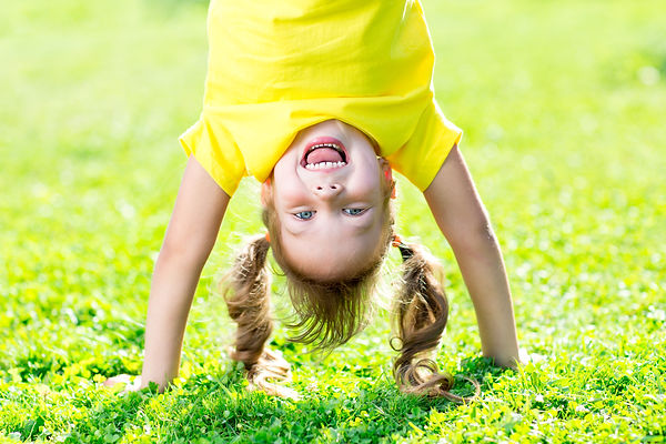 Portraits of happy kid playing upside down outdoors in summertime standing on hands on gra