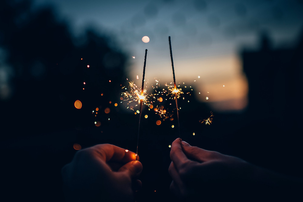 Two hands each holding up sparklers; the sparklers are halfway burned through; a blurry outdoor sunset in the background.