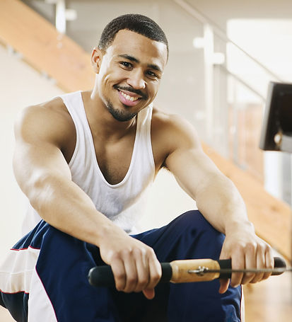 Pelvic-Floor-Acupuncture-Restore-Dry-Needling-A-smiling-man-on-a-rowing-machine
