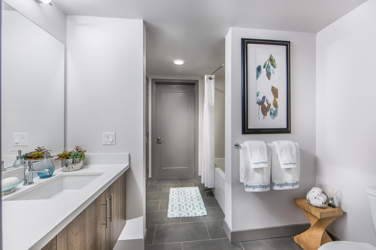 Access Apartments bathroom white walls and gray floor