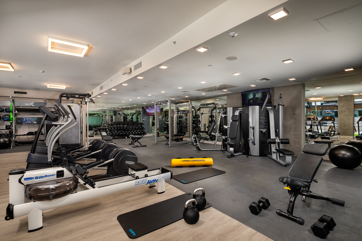 Trademark Apartments fitness room with bicycles, kettlebells, and weights