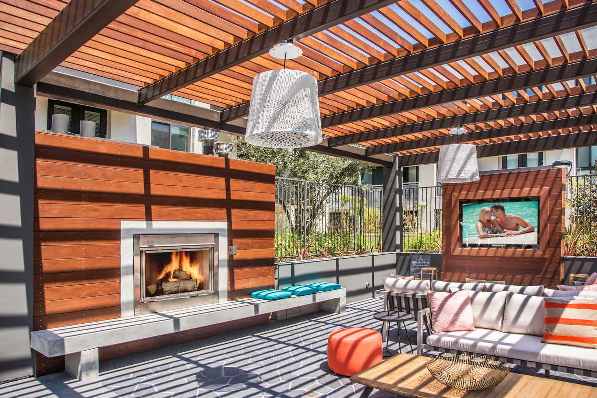 Outdoor fire place with television and couches Access Apartments