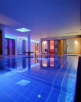 Schwimmbad mit Laconium, Dampfbad, Sauna und Whirlpool. Differenzierte Lichtstimmung durch LED-Beleuchtung in blau, rot, grüntönen.