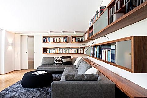 Individuell gestaltetes Bücherregal vom innenarchitekten in bestem Design. Ausführung vom Schreiner in Nussbaum natur. Schiebeelemente in satiniertem Glas. Leseleuchten mit schwenkbarem Arm, individuell einstellbar zum besseren Komfort. Reagl für hohe und niedrige Bücher. Couchgarnitur von B&B italia in grauem Stoff mit Designer Sitzkissen. Pouf zum abstellen von Accessoieres als Wohnzimmertisch. Hochfloriger Teppich in anthrazit. Exklusives Design für individuelle Kunden mit Geschmack und Stil.