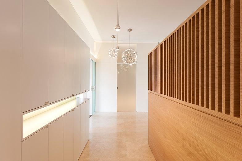 Exklusives Foyer in Designer Villa. Hochwertiger Möbelbau mit intergreierter LED Beleuchtung. Beleuchtung mit Leuchten von Moooi und Tobias Grau Falling. Garderobe mit raumhhoher Schiebetür.
