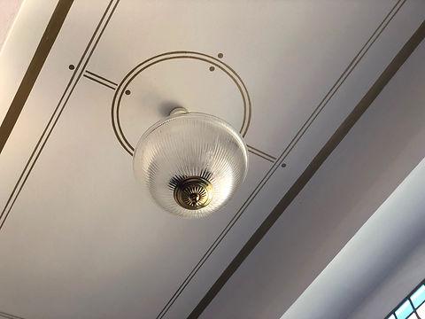Deckenfries unter Treppenlauf. Ornamentik im Judenstil Design mit Glasleuchten. Denkmalpflegerisches Design in alter Handwerkskunst.