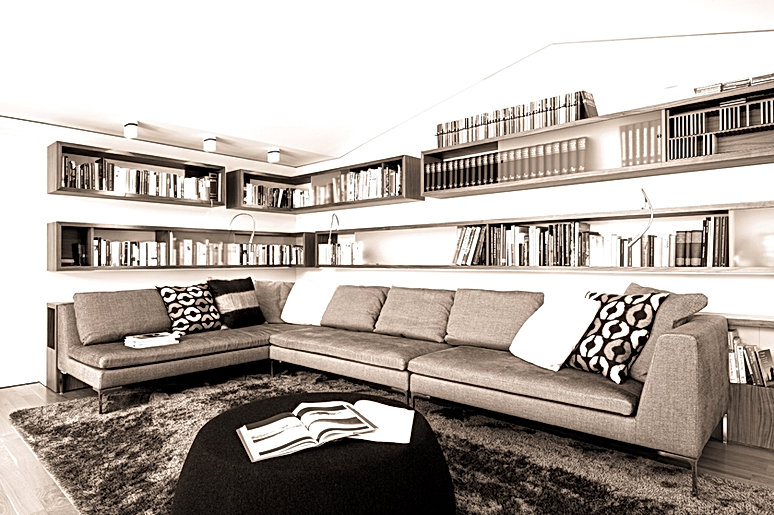 Innenarchitektur und Design im Möbelbau in individueller Schreinerarbeit. Bibliothek im Wohnzimmer mit flexibler Beleuchtung zum lesen. Ausführung der Möbel in Nussbaum natur mit Schiebeelementen.