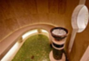 Dampfbad in Naturstein aus gespachteltem Travertin. Massiver Naturstein als Rückwand, rund geschnitten. Sitzbank in Naturstein mit massiven Steinkugeln aus Auflager mit integrierter Beleuchtung. Grünes Glasmosaik mit Goldeinlagen von Sicis nach Fliesenplan verlegt, mit zentralem Bodenablauf. Dampfsäule aus Keramik und Naturstein