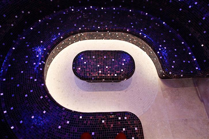 Laconium mit Sicis Glasfliesen nach Fliesenplan verlegt. Integrierte, farbige LED- Beleuchtung mit wechselnden Farbstimmungen für Wohlfühlbaden. Boden in Natursteinmosaik aus Travertin.