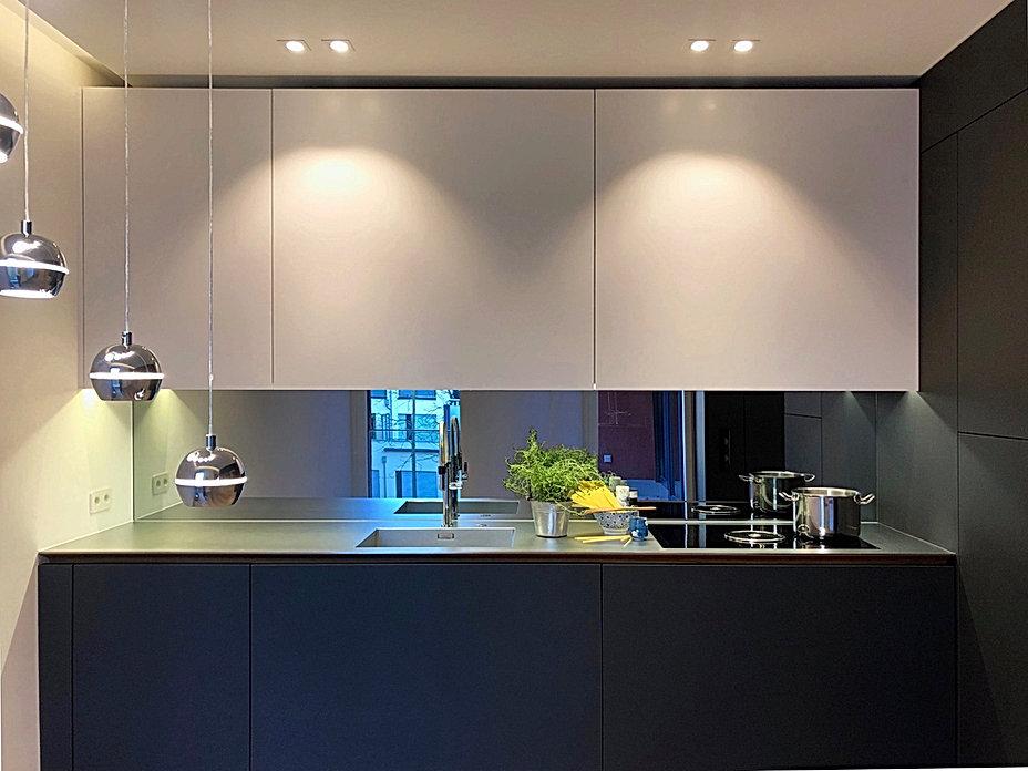 Designer Küchenfront in weissem Corian mit grossflächige, grifflose Schiebetüren mit Softclose. Rückwand mit Spiegelglas und integrierter Beleuchtung der Oberschränke. samtige Haptik der Oberfläche