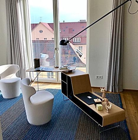 Geschmackvolles homeoffice individuell vom Designer gestaltet für Penthouse in Stuttgart mit Blick über die Dächer. Ausstattung mit Sesseln und Büroarbeitsplatz von B&B italia. Schöne Farbstimmung aus blauem robustem Teppich auf rustikaler Eiche, hellen Vorhängen mit verdeckter Vorhangschiene und dunklelbrauner Wand. Beleuchtung als Eingebaute Deckenstrahler zum schwenken, Wandleuchte und schwenkbaren Aufbaustarhlern.