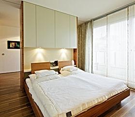 Gästezimmer mit Einbauschränken, Bett mit Rückenteil zum anlehnen in Nussbaum natur. Oberschränke mit integrierter Beleuchtung und Schiebetüren. Bettdesign vom innenarchitekten. Vorhänge und Bettwäsche vom Dekorateur nach Materialplan individuell erstellt.