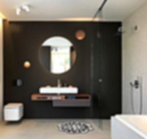 Designerbad mit hinterleuchtetem Rundspiegel vor dunkler Wand. Runde Einbauleuchten von Bechter. Waschtisch von lauffen auf individuell geplantem Unterschrank in Nussbaum.
