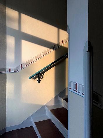 Neugestaltung eines Treppenhauses aus der Gründerzeit in Dresden Striessen. Neu entwickeltes Friesdesign. Restaurierung des bestehenden Handlaufes mit Originalbefestigungen in Metall. Treppenstufenbelag in Linoleum mit seitlicher Bordüre.