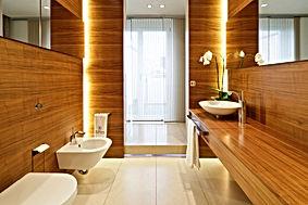 Gästebad mit exklusivem Design. Ausstattung mit WC und Bidet von italienischen Herstellern. Natursteinboden mit individuellem Fugenbild und hinterleuchtetem Podest. Hochwertige Schiebe-Vorhänge als Sichtschutz
