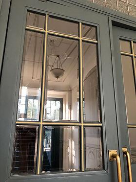 Denkmalpflegerische Instandsetzung einer Foyertür zum Treppenhaus mit geschliffener Verglasung, Bügelgriff in Messing. Deckenornamente am Unterseite der Treppenläufe in handwerklicher Maler Ausführung.