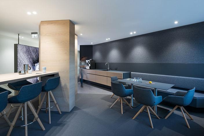 Lounge im Büroalttag eines Headquaters in Augsburg. Individuelles Design vom Innenarchitekten. Lichtgestaltung mit direktem und indirektem LED Licht. Küchenausstattung mit Spülmaschiene, Kühlschrank, Kaffeemaschiene und Stauraum für Gläser und Küchenutensilien. Individueller Möbelbau vom Schreiner in Eiche natur und robusten Oberflächen in Schichtstoff. Leuchtwände als Trennwand zu Büroräumen und Sichtschutz. Flächige LED-Lichtwand mit Motiven aus dem Weltall.