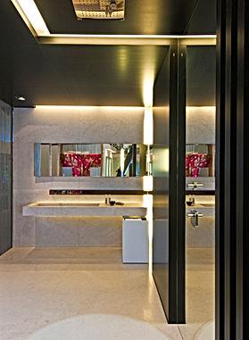 Klare Linienführung in tradionellem Baddesign. Natürliche Materialien in Naturstein und Naturholz, kombiniert mit Spiegel und Chrom. Individuelles Lichtkonzept für Messestand mit Waschtisch, Dusche, und Stauraum für Badaccessoires.