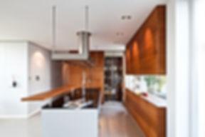 Küche in Mahagonieoptik mit grifflosen Türen gestaltet. Weinlagerschrank imit Glastür und Holzböden mit Natursteinwand. Kücheninsel in Alubeschichtung und schwarzer Granitarbeitsplatte mit flächenbündiger Herdplatte und Einbauspüle sowie integrierter Spülmaschine. Tresen in Massivholz aufgeständert. Massanfetrigung der Ablufthaube in Edelstahl mit integrierter Beleuchtung und Abluft über Dach. Stauraum mit Fensterblick zur begrünten Terrasse