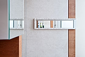 Natursteinplatten aus Travertin als Wandverkleidung in exklusiv gestalteter Dusche. Ablage für Badaccessoires in Naturstein mit Spiegelrückwand