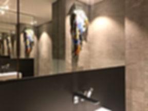 Besonderes Baddesign für aussergewöhnliche Ansprüche. Gestaltung mit grossformatigen Feinsteinzeugfliesen in Naturoptik aus italienischer Produktion. Exklusives Fugenbild mit Kanten auf Gehrung geschnitten. Flächenbündiger Übergang zum Möbelbau mit beschichtetem Linol Desktop in schwarz. Edle Wandarmaturen von Dornbracht. Spiegel zur optischen Raumerweiterung.