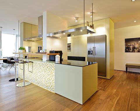 Hochwertige Kücheninsel mit hinterleuchtetem Glasmosaik, Arbeitsplatte in schwarzem Granit mit flächenbündigem Induktionsherd. Sonderanfertigung einer Edelstahl Abzugshaube mit integrierter Beleuchtung. Kühlschrank mit Icecrasher und Kaffeeautomat in Edelstahl. Bartresen aus Naturholz. Bodenbelag mit Dielen in Nussbaum Massiv