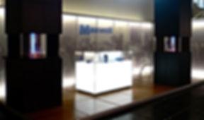 Messestandinsel für Besprechung und Ausstellung. Beleuchteter Korpus mit Stauraum für Exponate in satniertem Plexi. Ausstellungssäulen als Objekt- und Warenträger sowie Besprechungsinseln mit Objektbeleuchtung.