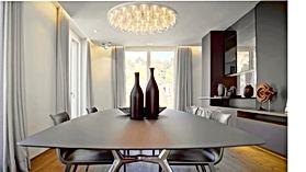 Esstisch aus satiniertem Glas von Rimadesio für 6 Personen mit Metallgestell als Fuss. Stühle in Leder von Freifrau mit Tellerfuss in poliertem Metall. Esstisch Leuchte von Artemide. Individuelles Lichtdesign mit Allgemeinbeleuchtung und Akzentlicht. Hinterleuchtet Deckenvoute mit verdecktem LED-Lichtband und unsichtbarer Vorhangschiene
