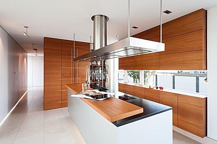 Exklusive Planung und individueller Innenausbau für besonder Kundenwünsche. Möbelbau in Massivholz mit grifflosen Türen. Differnziertes Lichtkonzept aus Einbaustrahlern und Occhioleuchten. Abzugshaube mit inegriertem LED-licht und Abzug über Dach.