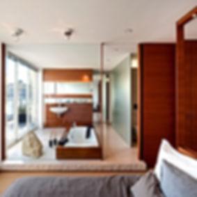 traumhafte Badewanne bodenbündig in Mahagoni, Designarmaturen und Naturstein mit satinierten Spiegeln