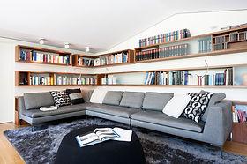 private Bibliothek mit Regalböden in Nussbaum. Davor Couch und Pouff von B&B in grauem und schwarzem Stoff und designten Sitzkissen. Regal für Bücher mit schwenkbarer Beleuchtung