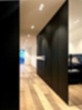 Schrankwand in Linol Desktop beschichtet mit Massiver Eiche. Flächenbündige Türen, grifflose Schranktüren. Stimmungsvolle Lichtgestaltung mit flächenbündigen Einbaustrahlern und Möbelleuchten. Möbel mit oberschrank und Unterschrank sowie Zwischenablage mit integrierter Steckdose.