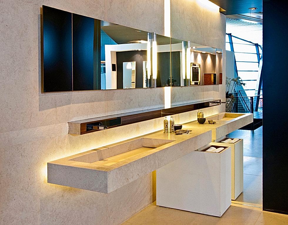 Marmorbad in Sanitärausstellung von Gienger. Boden und Wand in Naturstein Limestone. Intarsie mit bruchrauher Kante. Waschtisch in Naturstein auf integriertem Stahlgestell schwebend vor der Rückwand montiert. Individuelle Gestaltung durch den Designer für exklusive Bäder. Spiegel mit integrierter Spiegelleuchte. Optische Raumverdoppelung durch raumhohe Spiegelwand. Schwarze Decke mit Einbaustrahlern in MDF. Ablage in poliertem Edestahl mit integreirete Waschtisch Armatur von Gessi.