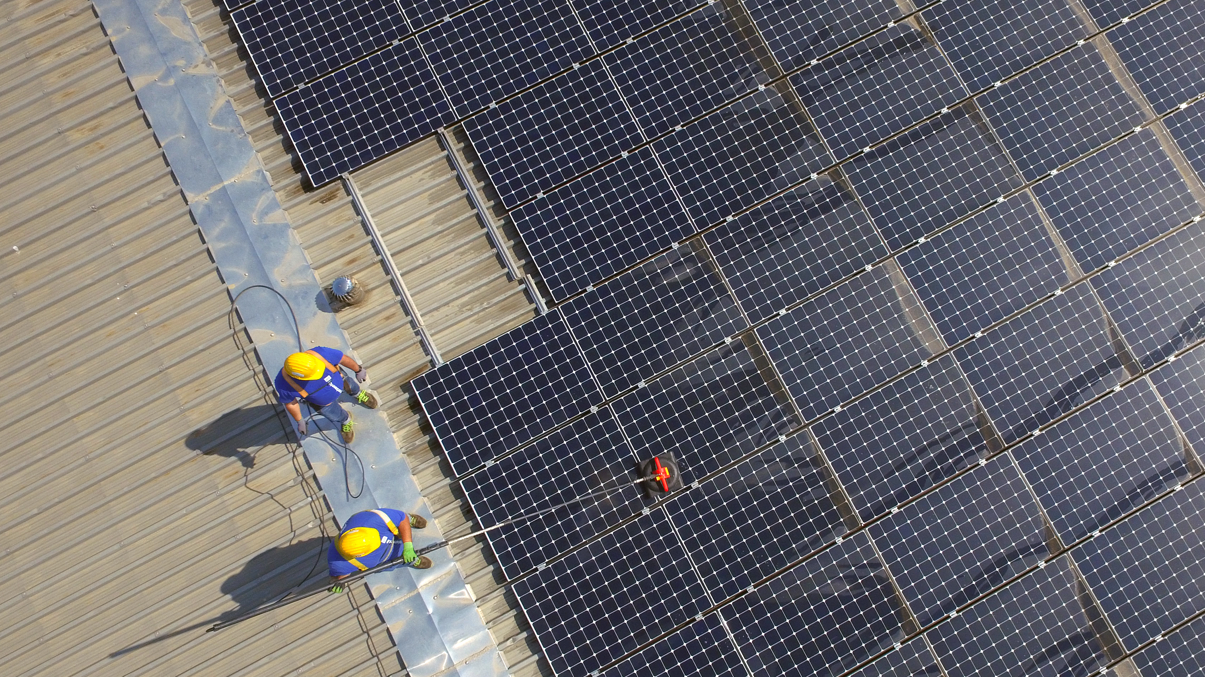 workers on the roof clean solar panels