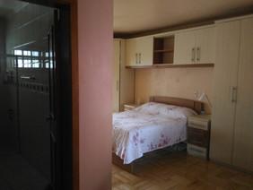 Dormitório com banheiro privativo e sacada