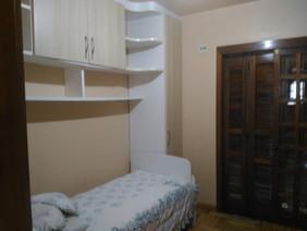 Dormitório simples com sacada