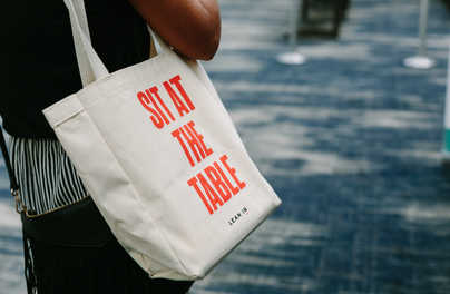 Slogany Lean In - Sit at the Table (zasadni za rozhodovací stôl), Proceed and Be Bold (napreduj a buď odvážna), Raise Your Hand (dvihni ruku, buď proaktívna)