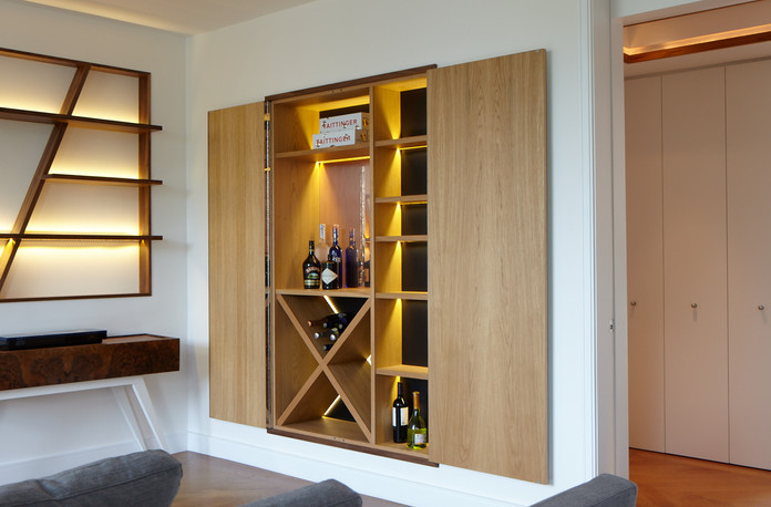 The surprise effect of Brompton drinks cabinet is given by the contrast between the outside and the inside. The outside has a mirror door feature with a walnut frame, whereas the inside is completely in oak with a black background. A copper mirror is positioned in the center.