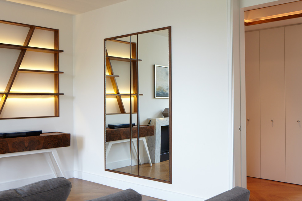 The picture shows the living room of the Brompton penthouse. It features the Brompton bookshelves, the Brompton console table, the Brompton drink cabinet with open doors and the Pelham coffee table, on a bespoke chevron wood floor. An interior space designed by Ivar London interior design.