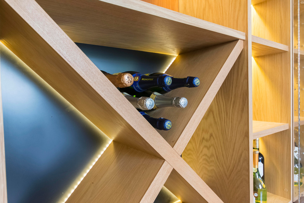 The picture shows the solid oak wine rack, the black spray painted back and the recessed LED light strip of an inside view of the Brompton drink cabinet designed by Ivar London interior design and hand made in London.