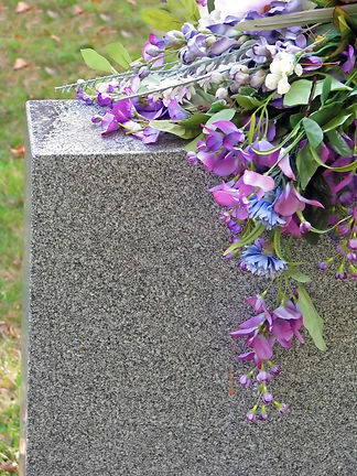 silk flowers on a cemetery grave tombsto