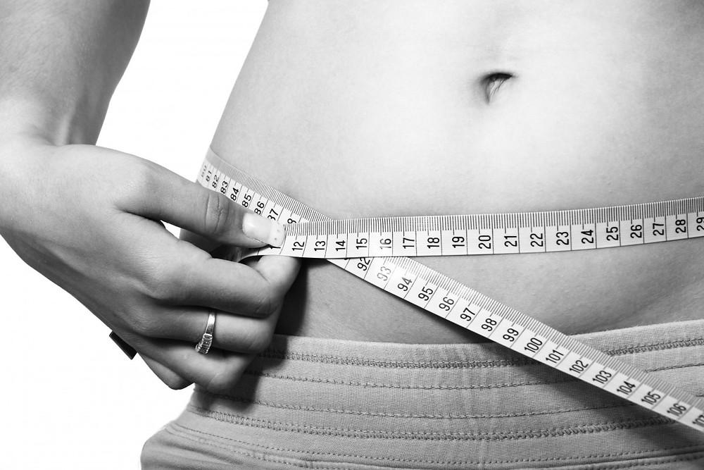 abdomem feminino com fita métrica em volta. imagem em preto e branco