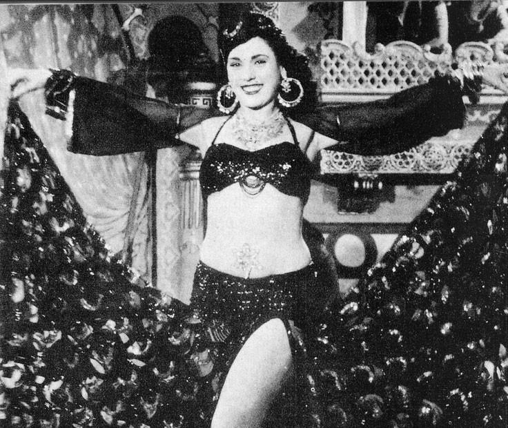 famosa bailaria e atriz egípcia, Taheyya Karioca, produzida com seu figurino de dança, com os braços abertos segurando as pontas da saia